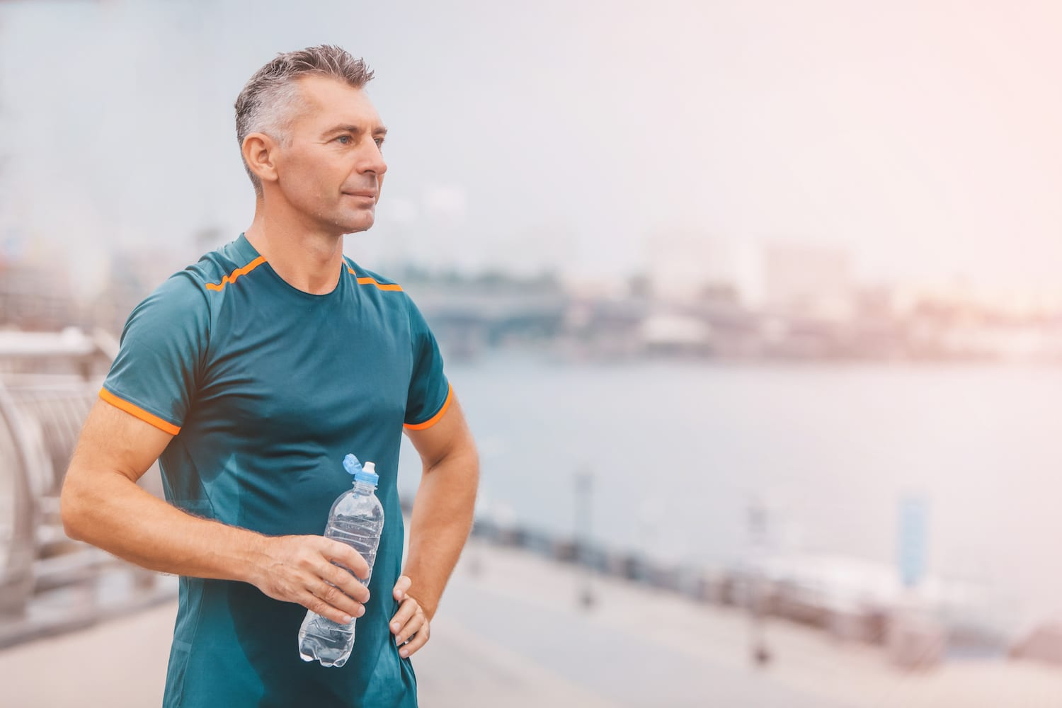 Portrait of healthy athletic middle aged man with fit body holding bottle of refreshing water, resting after workout or running. on the riverside. vintage color | Acadian Hearing