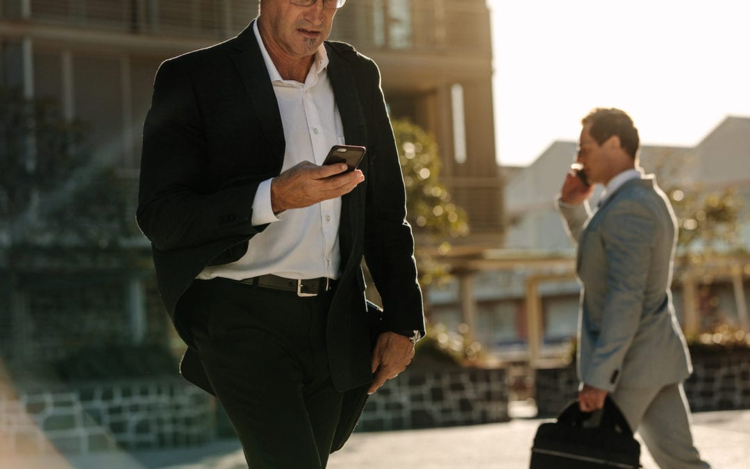 Men using mobile phone while commuting to office | Acadian Hearing