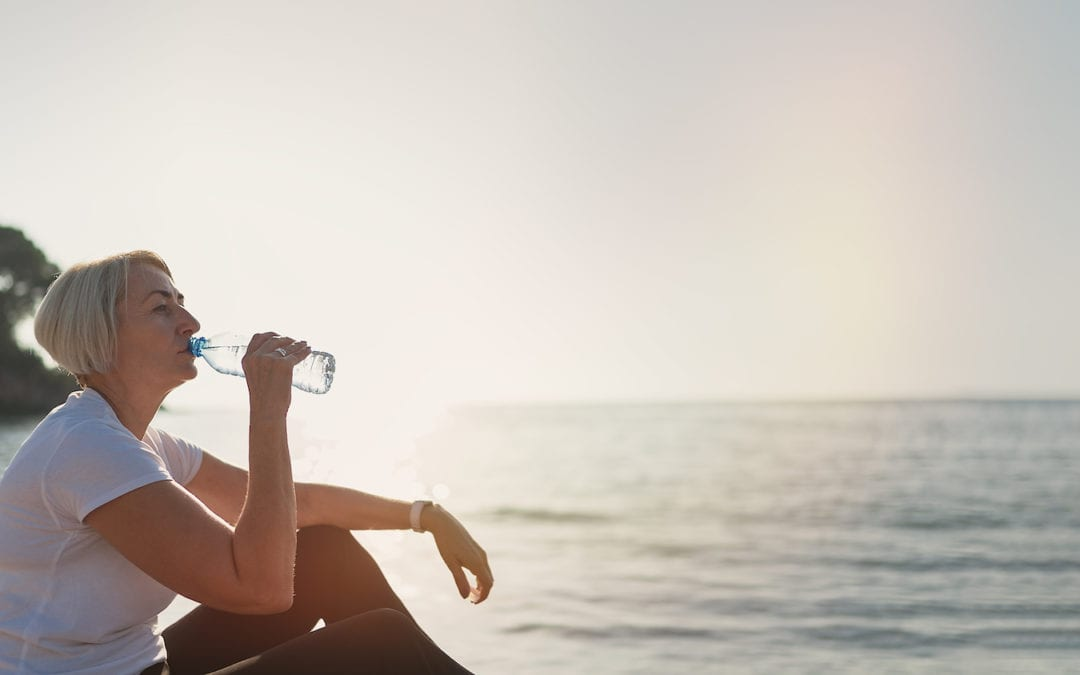 Mature woman drinking water during sunset after jogging. Senior lady sitting on the beach against the backdrop of the sea | Acadian Hearing
